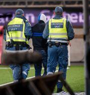 Supportern förs bort av vakter. MICHAEL ERICHSEN / BILDBYRÅN