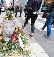 Ett betonglejon täckt av blommor på Drottninggatan efter terrorattacken. Fredrik Sandberg/TT / TT NYHETSBYRÅN