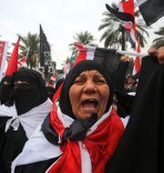 Demonstranterna var klädda i svart, vitt och rött. AHMAD AL-RUBAYE / AFP