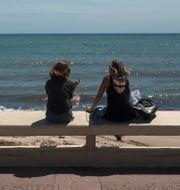 Två kvinnor som sitter vid stranden. Daniel Cole / TT NYHETSBYRÅN