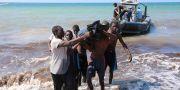 Räddningsarbetare bär i land en död kropp vid Tajouras kust, öster om Tripoli. Bilden är tagen den 20 juni.  HANI AMARA / TT NYHETSBYRÅN