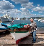 En äldre man pysslar om sin båt på den italienska ön Sardinien – en av världens fem blå zoner. Shutterstock