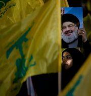 En Hizbollah-supporter håller upp en bild på  Hassan Nasrallah. Hussein Malla / TT NYHETSBYRÅN
