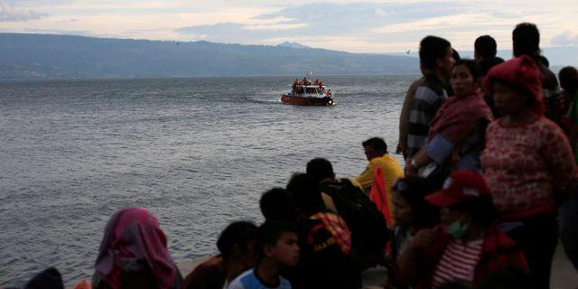 Människor samlas och följer räddningsaktionen. BEAWIHARTA / TT NYHETSBYRÅN