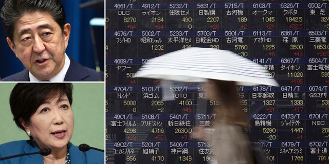Abe, Koike, kvinna som går förbi tavla med kurser från Tokyobörsen. TT