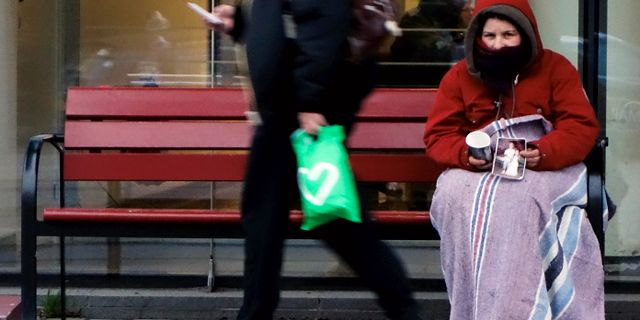En kvinna tigger pengar utanför Södersjukhusets entré.  Hasse Holmberg / TT / TT NYHETSBYRÅN