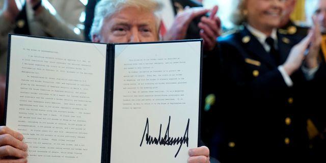 Trump signerar vetot. JONATHAN ERNST / TT NYHETSBYRÅN