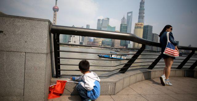 Illustrationsbild. Pojke med Kinaflagga och kvinna med USA-väska i Shanghai. Eugene Hoshiko / TT NYHETSBYRÅN