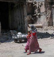 """Irakiska flickor går vid en förstörd byggnad i västra Mosul, Irak. På skylten står det """"Familjer finns här"""".  SAFIN HAMED / AFP"""