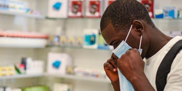 En man provar en ansiktsmask på ett apotek i Zambia. Emmanuel Mwiche / TT NYHETSBYRÅN