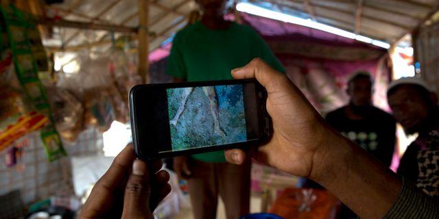 En flykting från Rakhine visar video-bilder av massgravar i Gu Dar Pyin för AP.  Manish Swarup / TT NYHETSBYRÅN