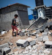 En pojke inspekterar skadorna efter en israelisk raketattack.  Khalil Hamra / TT NYHETSBYRÅN