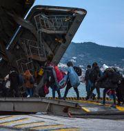 Migranter går ombord fartyget i hamnen i Mitilini på Lesbos. Panagiotis Balaskas / TT NYHETSBYRÅN