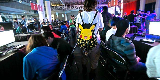 Person med pokémon-ryggsäck går igenom ett gäng gamers. Gerald Herbert / TT NYHETSBYRÅN/ NTB Scanpix