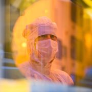 An associate is reflected in a 300-millimeter wafer in the clean room during a press tour of the new semiconductor factory of the Bosch company in Dresden, Germany, May 31, 2021. The chip factory will officially start working on June 7, 2021. Robert Michael / TT NYHETSBYRÅN