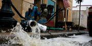 Vatten pumpas ut från en översvämmad butikslokal i New Bern, North Carolina.  EDUARDO MUNOZ / TT NYHETSBYRÅN