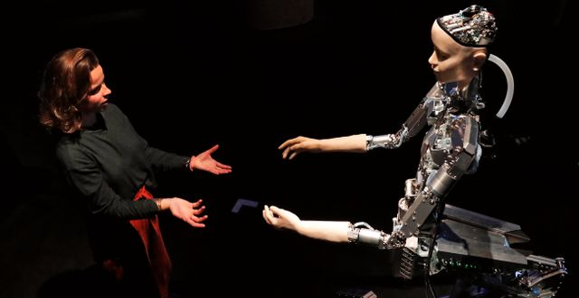 """Kvinna som interagerar med en robot på konstutställningen """"AI:More than Human"""" i London.  Frank Augstein / TT NYHETSBYRÅN/ NTB Scanpix"""