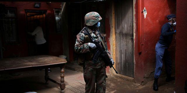 I Sydafrika vaktar polis och soldater så att människor följer nedstängningen.  Siphiwe Sibeko / TT NYHETSBYRÅN
