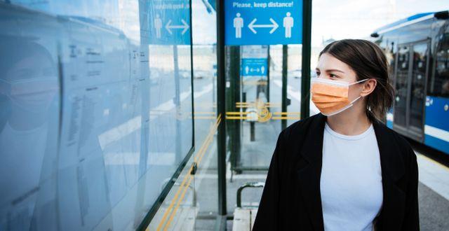 Kvinna med munskydd vid busshållplats.  Erik Simander/TT / TT NYHETSBYRÅN