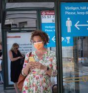 Kvinna vid busshållsplats i Stockholm/The Guardians artikel från 23 mars. TT/The Guardian