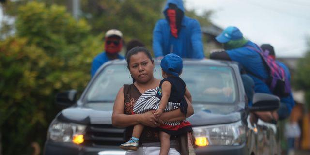 En kvinna håller sitt barn, i bakgrunden paramilitärer i området Monimbo. MARVIN RECINOS / AFP