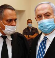 Motdemonstrant/Netanyahu (till höger) i rättssalen. TT