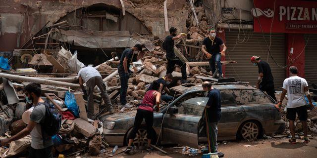Människor utanför en skadad byggnad i Beirut. Felipe Dana / TT NYHETSBYRÅN