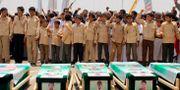 Barn framför kistor vid massbegravningen. STRINGER / AFP