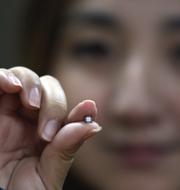Kinesisk kvinna håller i ett litet chip. TT