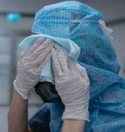 En sjuksköterska tvättar skyddsmask 90 efter ett pass på iva-avdelningen på Södertälje sjukhus Staffan Löwstedt/SvD/TT / TT NYHETSBYRÅN