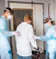 En undersköterska och en fysioterapeut utför rehabilitering av en tidigare covidsjuk patient. Pontus Lundahl/TT / TT NYHETSBYRÅN