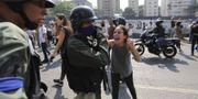 En kvinna i Caracas hejar på soldater som gjort uppror mot president Nicolás Maduro.  TT