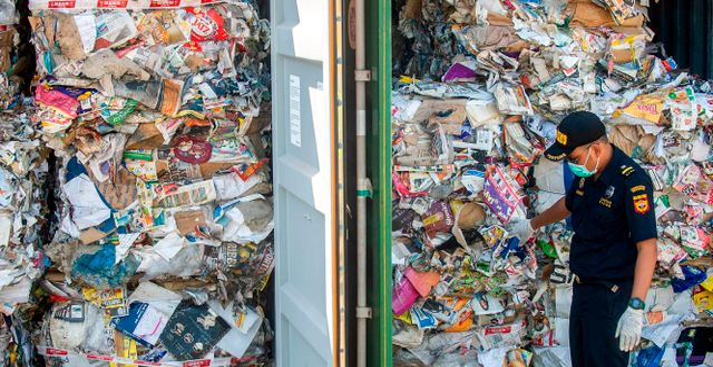 En tulltjänsteman inspekterar en container med avfall.  JUNI KRISWANTO / AFP