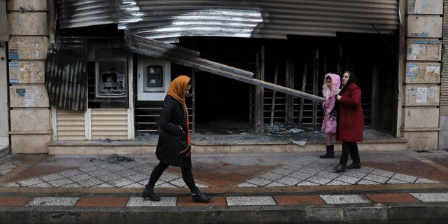 Shariar-invånare går förbi en bank som skadades i protesterna.  Vahid Salemi / TT NYHETSBYRÅN