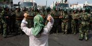 En uigurisk kvinna protesterar framför paramilitär polis i Xinjiang i juli 2009. Ng Han Guan / TT NYHETSBYRÅN/ NTB Scanpix