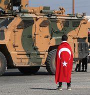 Ett barn bär en turkisk flagga framför ett turkiskt militärfordon i staden Tel Abyad i Syrien.  KHALIL ASHAWI / TT NYHETSBYRÅN