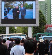 En storbildsskärm vid järnvägsstationen i Pyeongyang visar Kim Jong-Un skaka hand med Singapores premiärminister Lee Hsien Loong. Jon Chol Jin / TT NYHETSBYRÅN