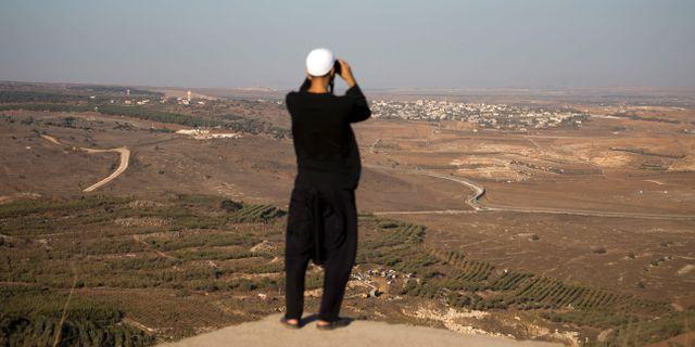 En man tittar på stridigheter mellan Bashar al-Assads styrkor och rebeller i Syrien från Golanhöjderna.  Ariel Schalit / TT / NTB Scanpix