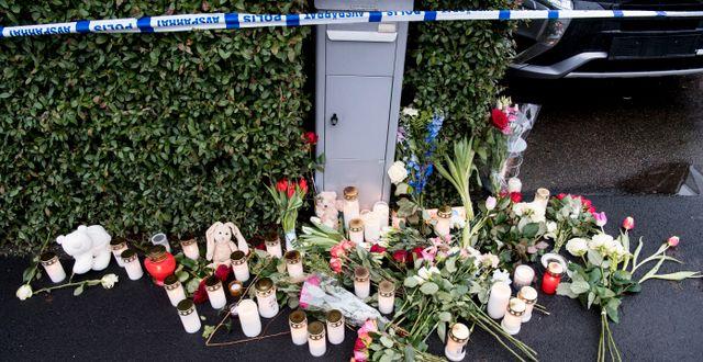 Blommor och ljus utanför polisens avspärrningsband kring villan i Bjärred på torsdagen. Johan Nilsson/TT / TT NYHETSBYRÅN