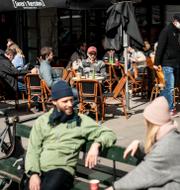 Danmarks statsminister Mette Frederiksen/danskar satt utomhus i solen när barerna återöppnade 21 april. TT