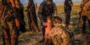 SDF-styrkor håller ett litet barn vid en säkerhetskontroll efter att barnet och dennes mot lämnat IS-fästet Baghouz. BULENT KILIC / AFP