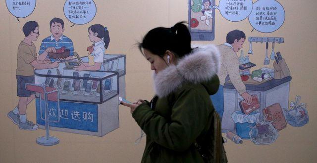 Arkivbild: Kvinna med Iphone i Peking. Andy Wong / TT NYHETSBYRÅN