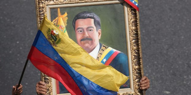 Anhängare till presidenten bär ett porträtt av Nicolas Maduro. Boris Vergara / TT NYHETSBYRÅN