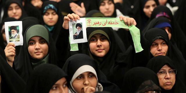 Kvinnor lyssnar på ett uttalande av Ali Khamenei i Teheran idag och håller upp bilder på ledaren. HANDOUT / TT NYHETSBYRÅN