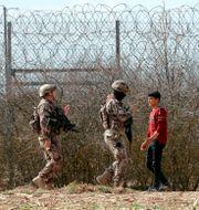 Två turkiska poliser patrullerar gränsen mellan Turkiet och Grekland i mars. Darko Bandic / TT NYHETSBYRÅN