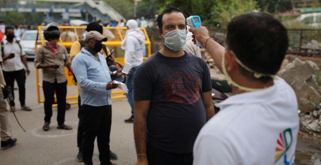 Människor i Indien screenas. Altaf Qadri / TT NYHETSBYRÅN