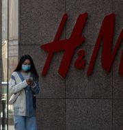 Kvinna utanför H&M-affär i Peking. Arkivbild. Andy Wong / TT NYHETSBYRÅN