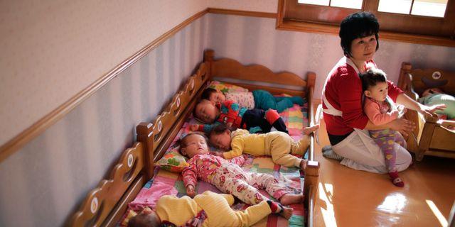 En kvinna sköter om barn på ett daghem vid en arbetsplats i Pyongyang. Wong Maye-E / TT / NTB Scanpix