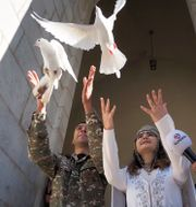 Ett brudpar släpper vita duvor utanför en kyrka i Nagorno-Karabach.  TT NYHETSBYRÅN