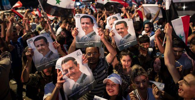 Syrier med bilder på al-Assad.  Hassan Ammar / TT NYHETSBYRÅN